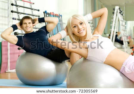happy cutie athletic girl and guy,  execute exercise on muscles belly  on balls and smile, in  sport-hall