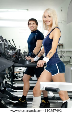 happy cutie athletic girl and guy,  execute exercise on  running track  and smile, in  sport-hall - stock photo