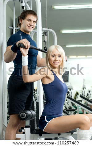 happy cutie athletic girl and guy,  execute exercise on sport-apparatus , in  sport-hall