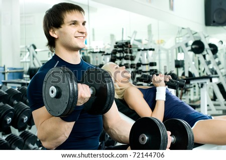 happy cutie athletic girl and guy,  exercise with dumbbells and smile, in  sport-hall - stock photo