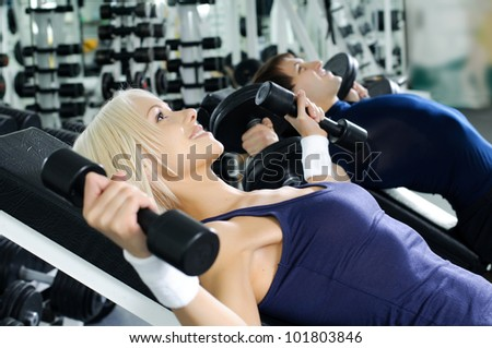 happy cutie athletic girl and guy,  lie exercise with dumbbells and smile, in  sport-hall