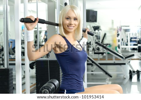 happy cutie athletic girl ,  execute exercise on sport-apparatus  and smile, in  sport-hall