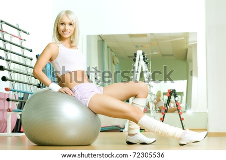 happy cutie athletic girl ,  sit  on fitnes balls and smile, in  sport-hall