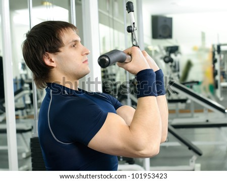 happy cutie athletic guy ,  execute exercise on sport-apparatus  and smile, in  sport-hall