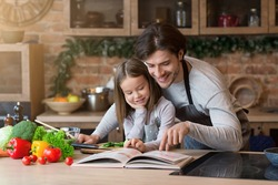 Happy dad and little daughter checking recipe in cookbook at kitchen together while cooking healthy lunch at home, free space