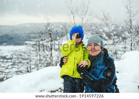 Happy dad and son at winter forest. Kid looking to monocular. Family winter holidays. Father and kid having fun together on nature. Father and son hiking in winter mountains.