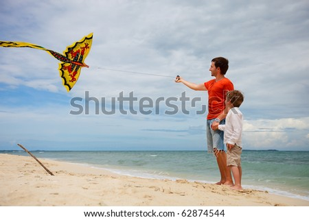 Happy dad and son flying kite together at tropical beach