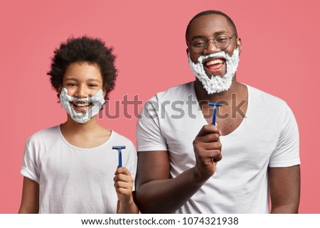 Happy dad and son with pleasant appearance, have shaving foam on faces, hold razors and going to shave, stand in frot of mirror in pink bathroom, have fun together. African kid imitates father Foto stock ©