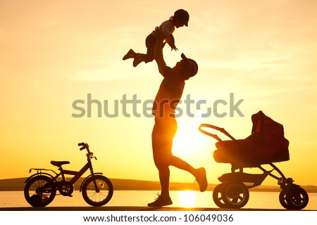 happy dad  daughter throws up into the sky next to the stroller at sunset