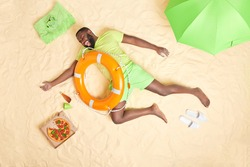 Happy dark skinned bearded man lies on sandy beach with lifebuoy over body has cheerful expression dressed in summer clothes has good mood rests at seaside surrounded by pizza parasol slippers