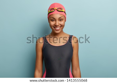 Happy dark skinned female going to swim, wears pink swimcap and goggles, has sporty body shape, isolated over blue background. Optimistic professional swimmer has training in pool, good mood
