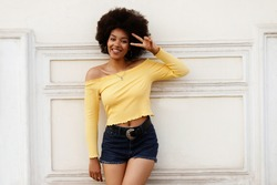 Happy dark-skinned girl against the wall.