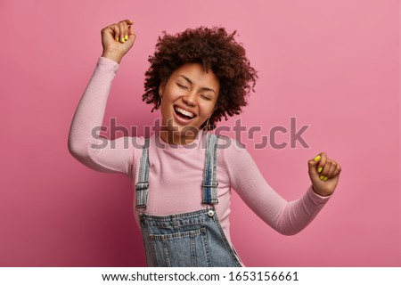 Happy dark skinned girl enjoys every moment of life, dances and moves, raises arms and clenches fists, closes eyes, has good mood, wears denim sarafan and turtleneck, isolated on pink background Foto stock ©