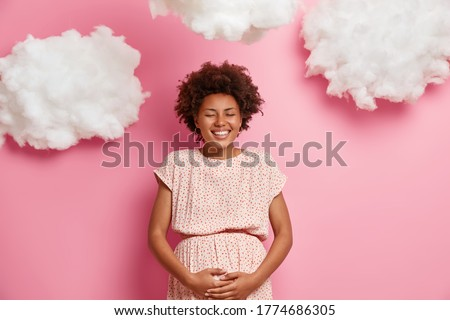 Happy dark skinned pregnant woman touches big belly, cares about future child, smiling expectant mother has good mood, stands with closed eyes, anticipates of becoming mom. Motherhood, expectation Photo stock ©