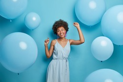 Happy dark skinned woman enjoys music at party, dances carefree, has fun and moves with rhythm of merry song, dressed in festive outfit, isolated over blue background with decorated air balloons.