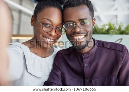 Happy dark skinned young male and woman bloggers make picture for profile, pose for selfie, share photos in social network accounts, wears spectacles, have broad smiles and white perfect teeth