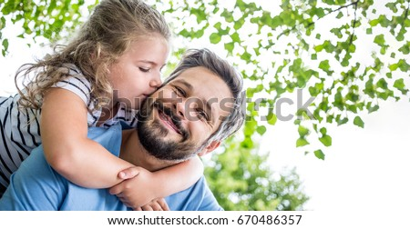 Happy daugther gives father a kiss and embrace him with love