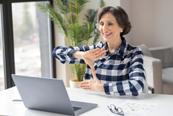 Happy deaf elderly woman uses sign language while video call using laptop while sitting in home office