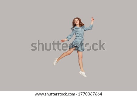 Happy delicate girl in vintage ruffle dress levitating with ballet dance move, hovering in mid-air and smiling joyfully, jumping trampoline, flying up. indoor studio shot isolated on gray background