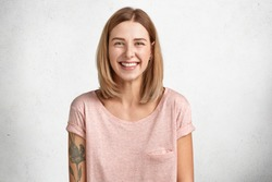 Happy delighted female with positive smile, has tattoo, smiles broadly, dressed in casual clothing, isolated over white concrete wall. Smiling adorable glad woman rejoices success and having weekends