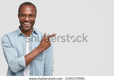 Happy delighted male manager involved in advertising company`s product, indicates with fore finger at blank copy space, wears denim shirt, has positive smile. Advertisement and ethnicity concept #1104119081