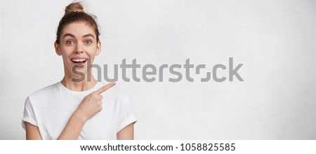 Happy delighted young female model with amazed expression, hair bun, dressed casually, isolated over white background with copy space for your promotional text or advertisment. Look there please