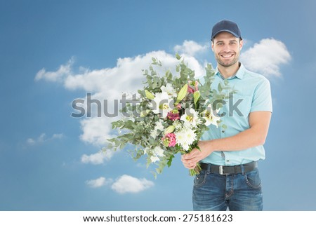 Happy delivery man holding bouquet against cloudy sky