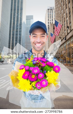 Happy delivery man holding bouquet against new york street
