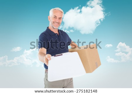 Happy delivery man holding cardboard box and clipboard against blue sky