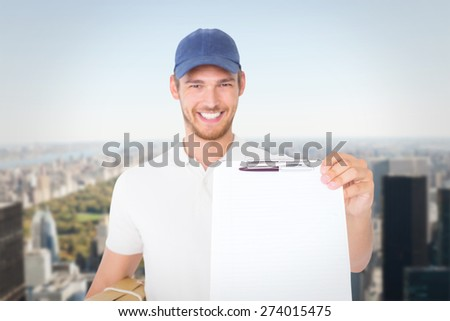 Happy delivery man holding cardboard box and clipboard against new york