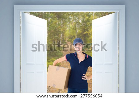 Happy delivery woman holding cardboard box against scenic view of walkway along lush forest