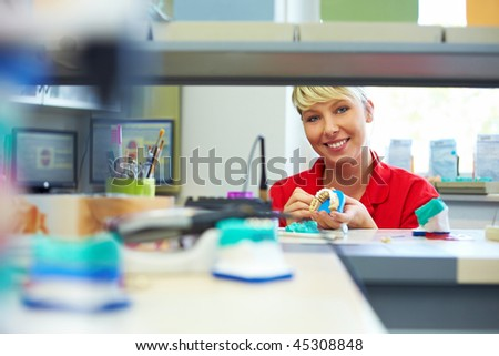 Happy dental technician working on a zircon bridge