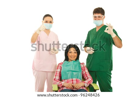 Happy dentists doctor and nurse showing okay and thumb up around smiling patient woman on chair isolated on white background