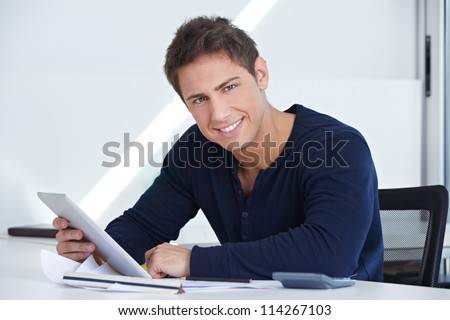 Happy designer sitting at his desk with a tablet computer in his hand
