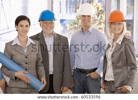 Happy designer team wearing hardhat in office holding architectural plan, smiling.?