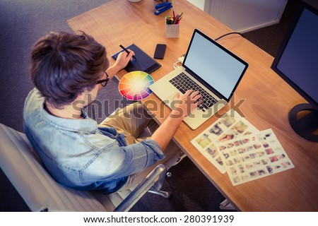 Happy designer working on his laptop in creative office