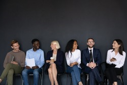 Happy different generations mixed race business people sitting on chairs in row line, isolated on black background with above copyspace. Smiling diverse job seekers chatting, waiting for interview.