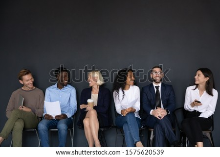Happy different generations mixed race business people sitting on chairs in row line, isolated on black background with above copyspace. Smiling diverse job seekers chatting, waiting for interview. Foto stock ©