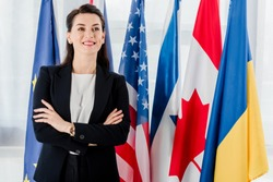 happy diplomat standing with crossed arms near flags