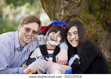 Happy disabled boy with cerebral palsy  in wheelchair surrounded by father and older sister, laughing
