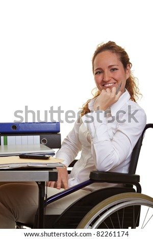 Happy disabled business woman at work on her desk - stock photo