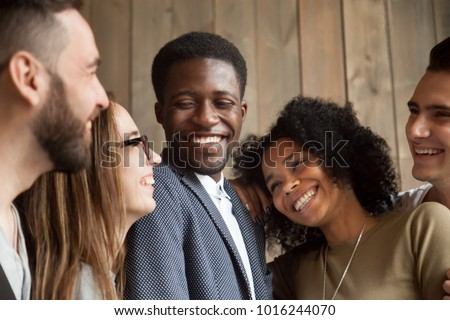 Happy diverse black and white people group with smiling faces bonding together, cheerful african and caucasian young multi ethnic friends having fun laughing embracing, multiracial friendship concept