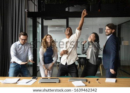 Happy diverse business people celebrating successful teamwork result, business achievement, good news, excited colleagues coworkers dancing in modern office, rejoicing victory, having fun
