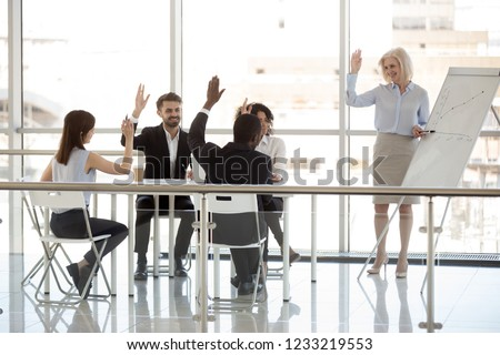 Happy diverse business people team interns group and mature mentor coach raising hands at office training as concept of teambuilding engagement, supporting agreement, knowledge, voting, involvement
