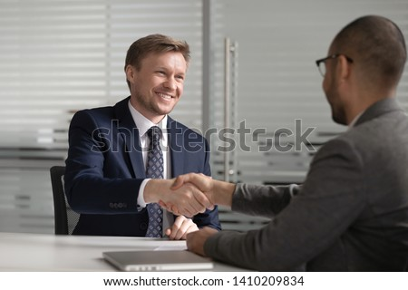 Happy diverse businessmen shake hands make business agreement at meeting, caucasian client customer handshake african investment advisor broker or bank manager thank for insurance loan services deal