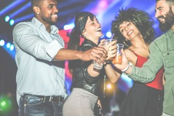 Happy diverse culture friends having party in club at night - Young people having fun cheering with cocktails at disco dance floor - Youth concept - Focus on black man hand - Vintage filter