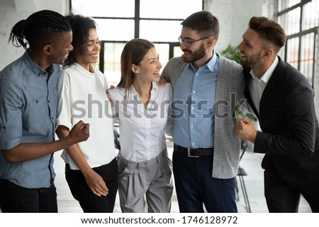 Happy diverse employees team celebrating success, business achievement hugging with smiling businesswoman team leader, standing in modern office, engaged in team building activity at meeting