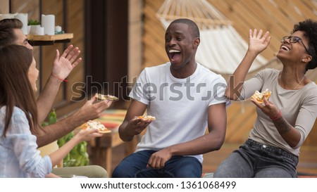Happy diverse friends listening to young man telling funny story making laugh sharing dinner, multi-ethnic students people eat pizza in cafe terrace outdoor talking having fun together at meeting