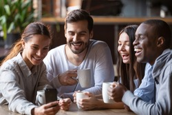 Happy diverse friends taking group selfie on cellphone in cafe, cheerful multiracial students making photo using snapshot app watching funny video on smartphone sitting at coffee shop table together