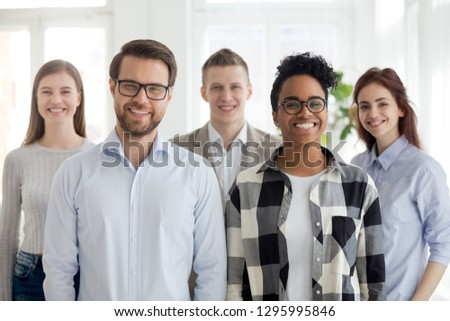 Happy diverse office workers group, multiethnic professional leaders and employees looking at camera, workforce sales team portrait, motivated international staff business people posing together